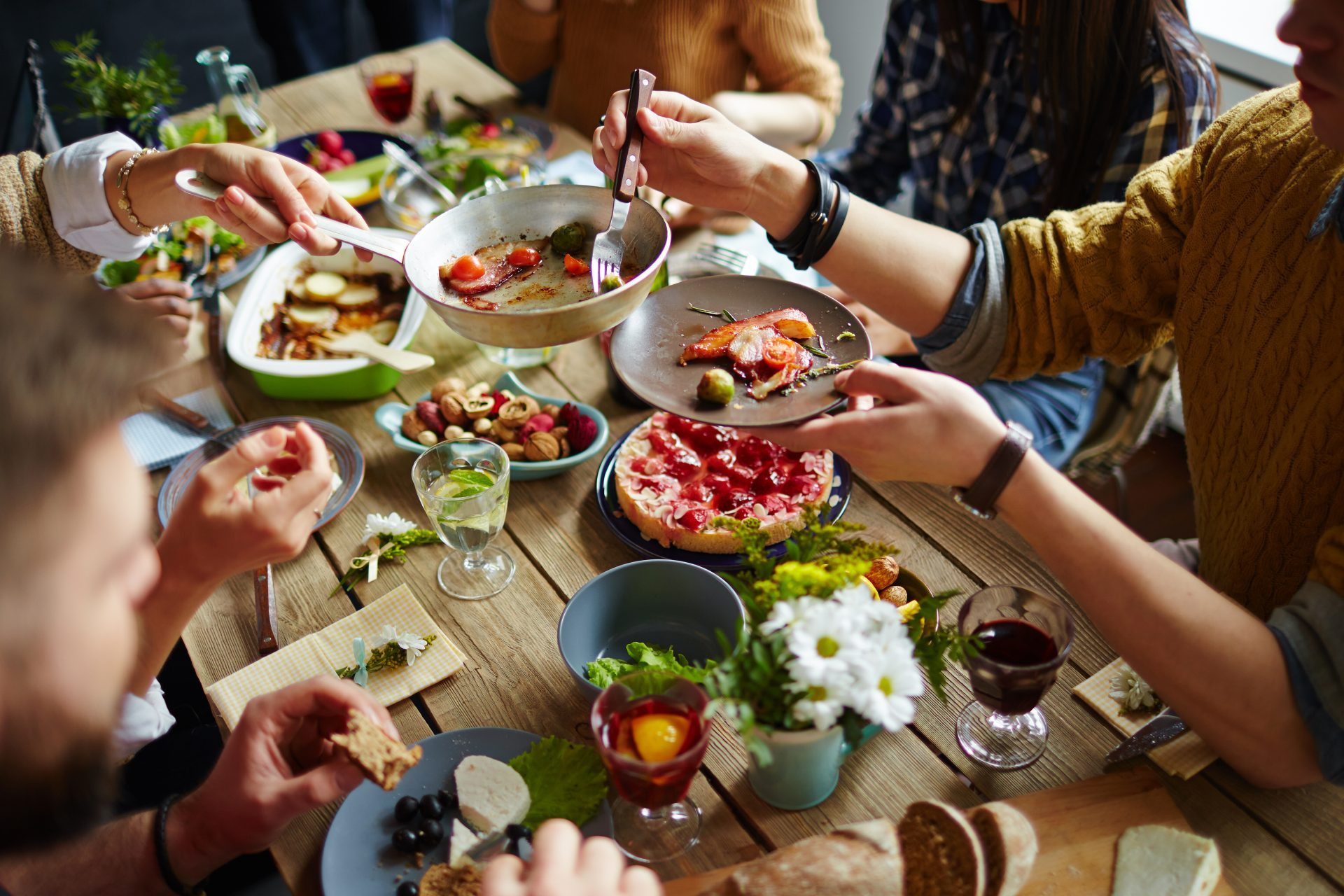 People sitting at dining table eating a family-style dinner