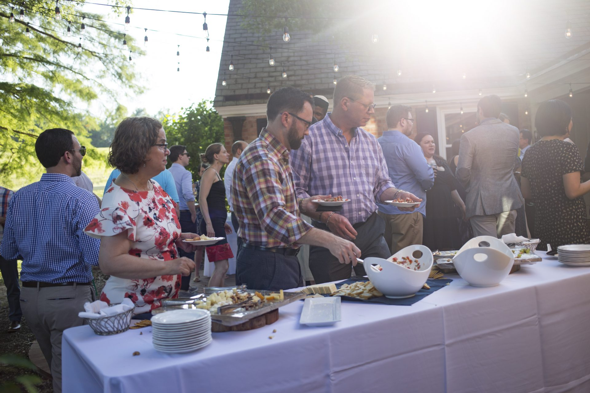 Event attendees getting food from an outdoor buffet at an event catered by Bleu Events
