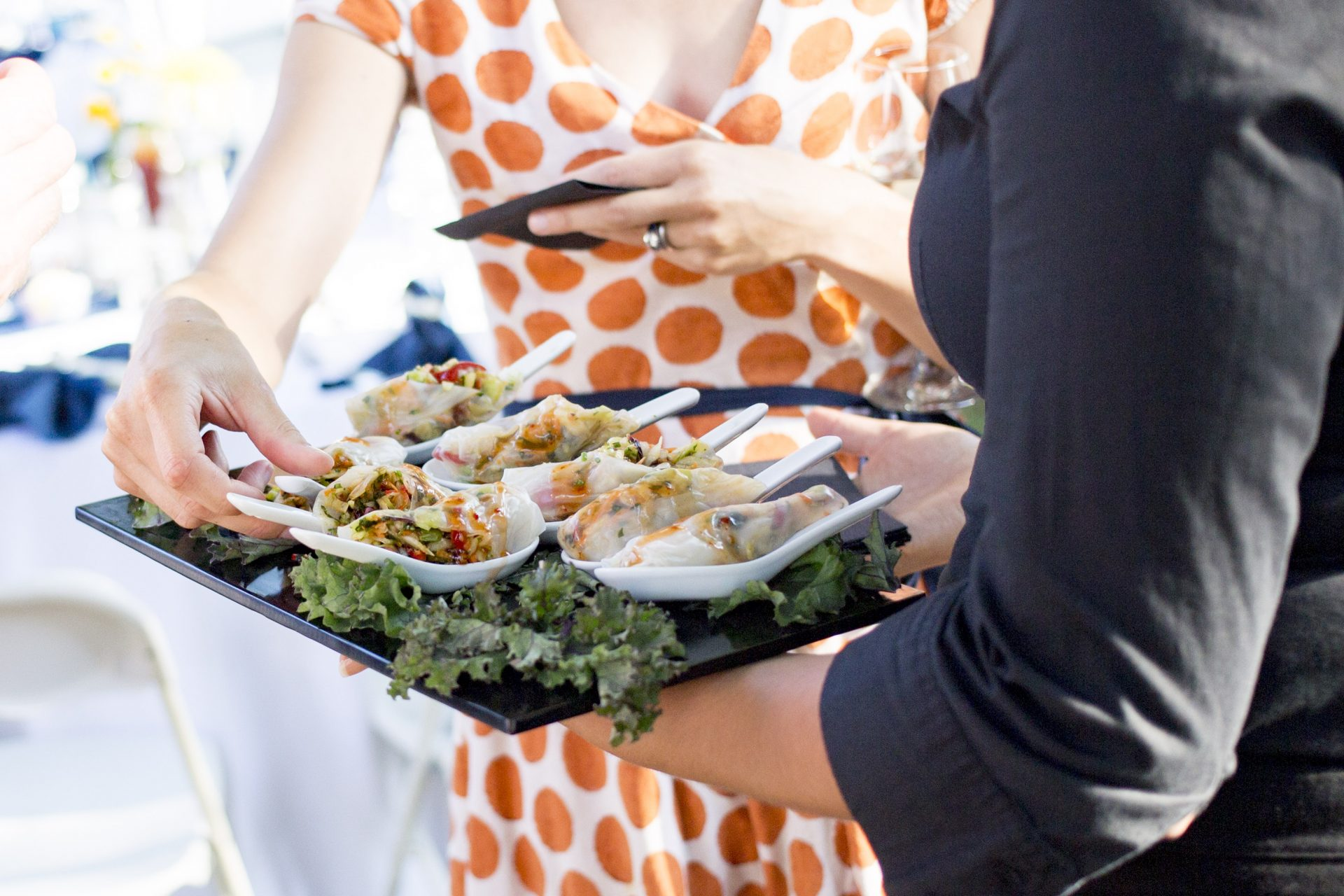Close view of a server serving an event attendee hors d'oeuvre at a corporate event
