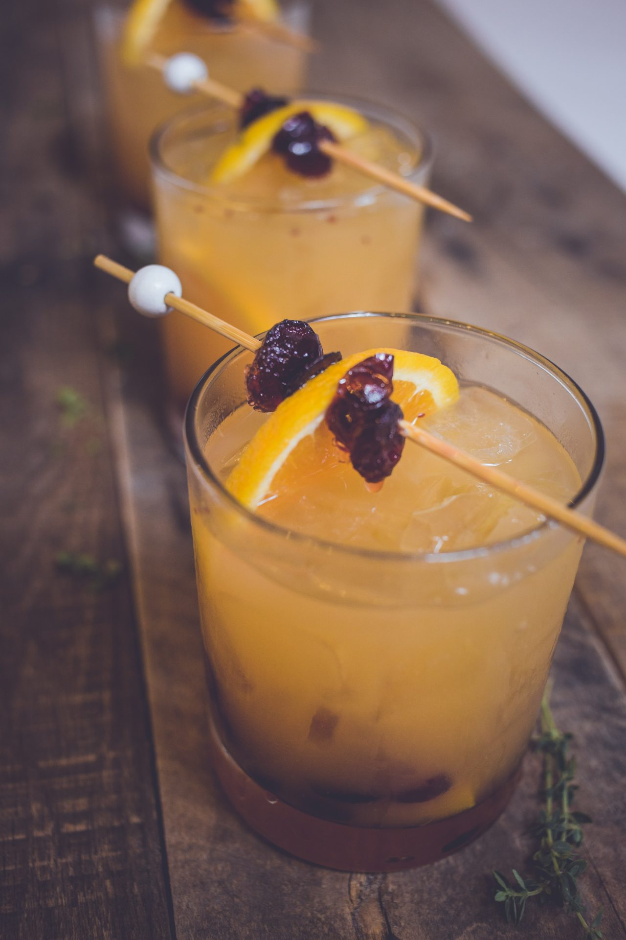 Craft cocktails garnished with an orange and cranberries by Bleu Events Catering