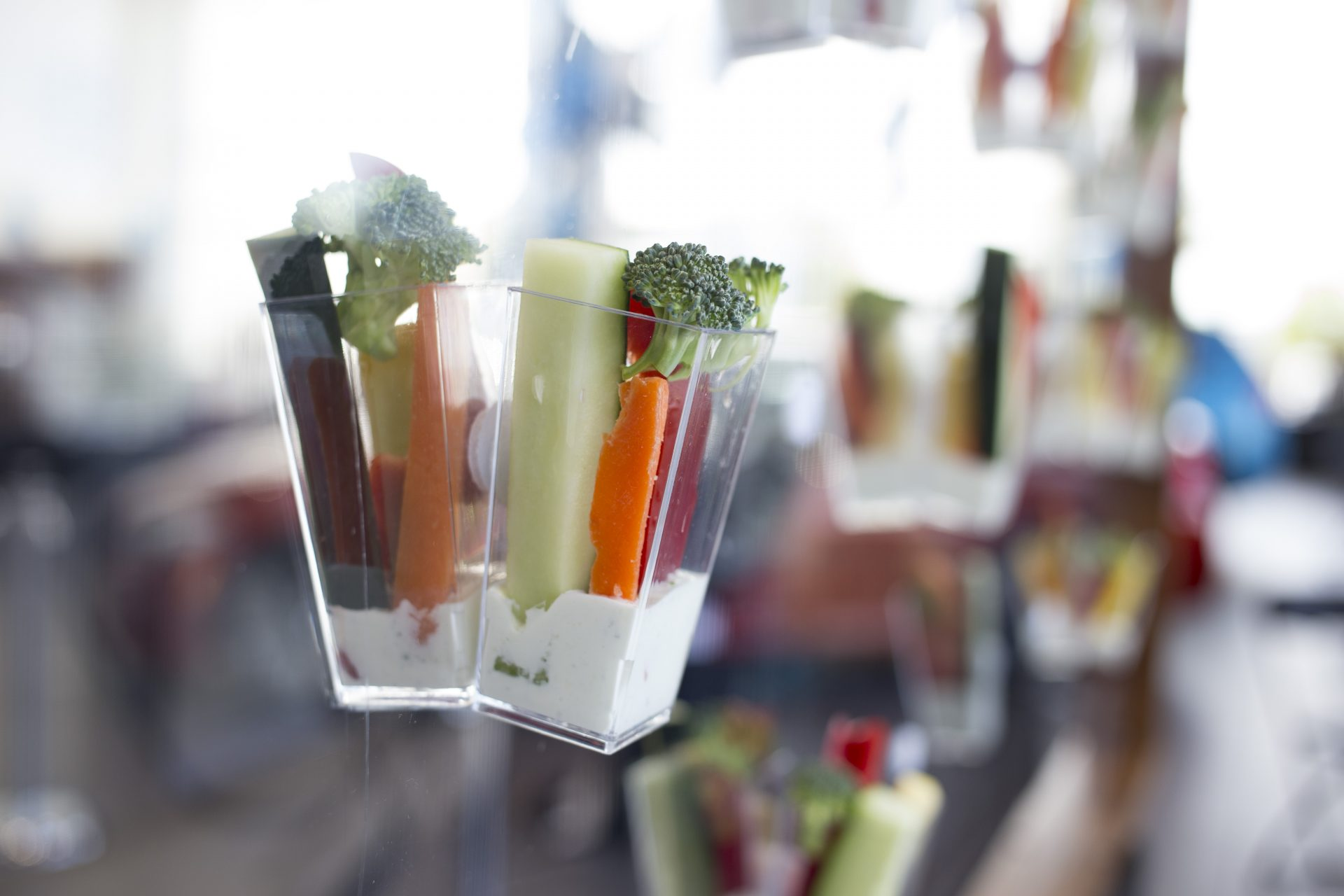 Close view of cups of crudités served on a modern food wall by Bleu Events
