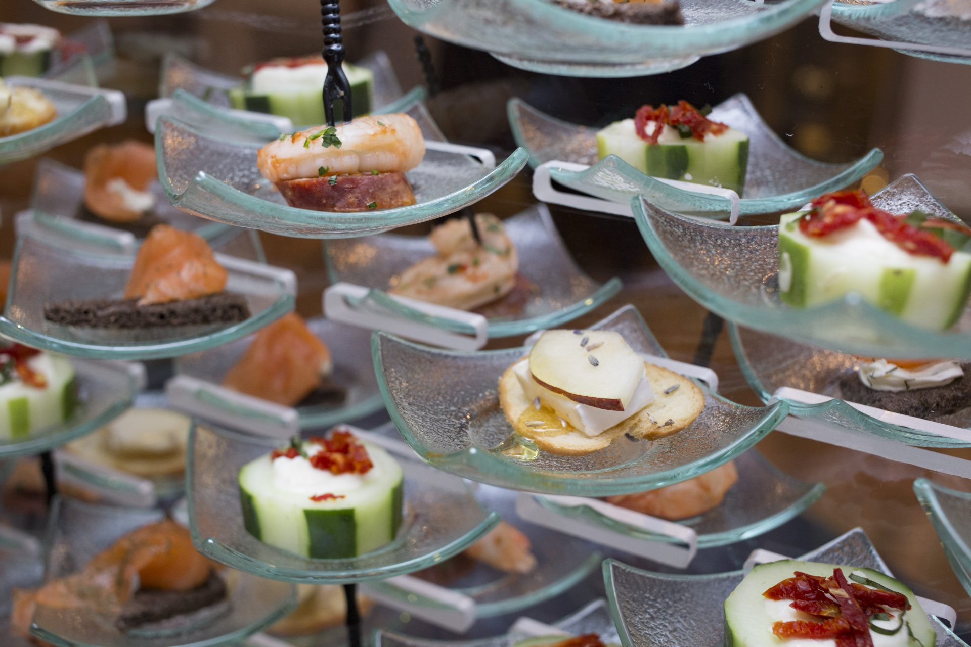Close view of an assortment of hors d'oeuvres served on a modern food display at an event by Bleu Events