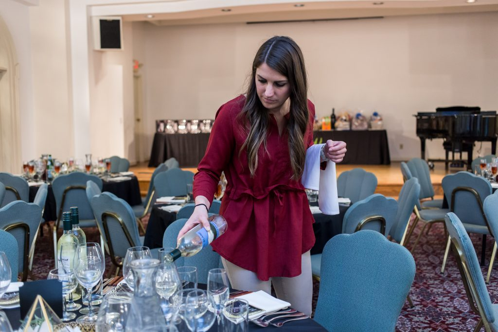A woman pours wine at an event