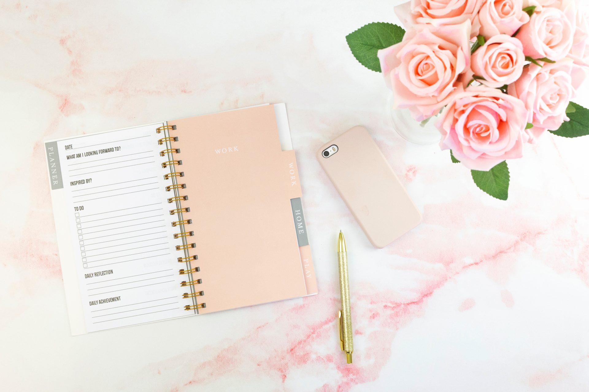 Planner with pen, phone and roses